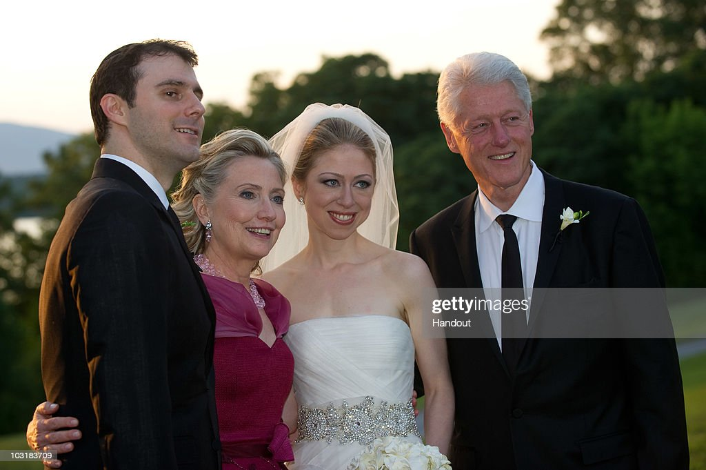 In this handout image provided by Barbara Kinney, (L-R) Marc Mezvinsky, U.S. Secretary of State Hillary Clinton, Chelsea Clinton and former U.S. President Bill Clinton pose during the wedding of Chelsea Clinton and Marc Mezvinsky at the Astor Courts Estate on July 31, 2010 in Rhinebeck, New York. Chelsea Clinton, the daughter of former U.S. President Bill Clinton and Secretary of State Hillary Clinton, married Marc Mezvinsky today in an interfaith ceremony at the estate built by John Jacob Astor on the Hudson River about two hours north of New York City.