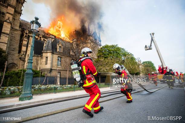 In this handout image provided by Brigade de sapeurspompiers de Paris firefighters battle the blaze at NotreDame Cathedral on April 15 2019 in Paris...