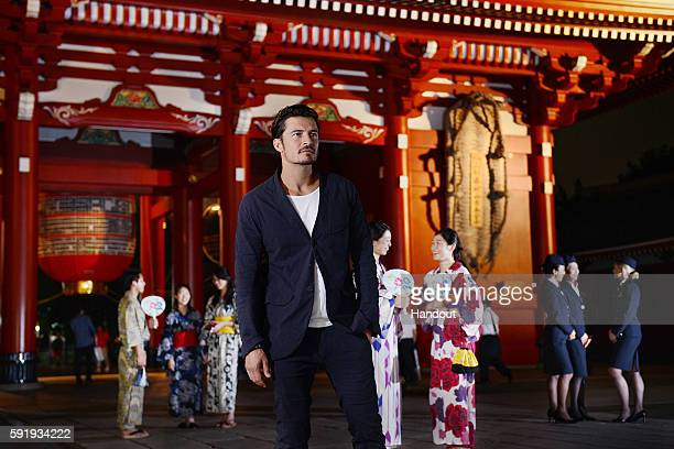 In this handout image provided by British Airways Orlando Bloom takes in the atmosphere with British Airways ambassadors at Hozomon inside Tokyo's...
