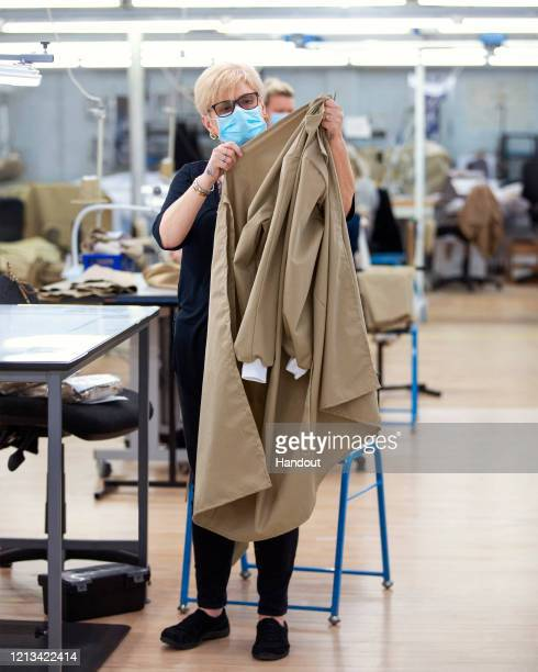 In this handout image provided by Burberry, a Burberry employee creates a gown at Burberry's factory in Castleford, England. The factory, which is...