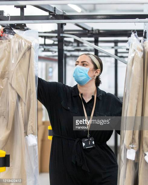 In this handout image provided by Burberry, a Burberry employee inspects finished gowns at Burberry's factory in Castleford, England. The factory,...