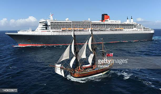 In this handout image provided by Carnival Australia the Queen Mary 2 is saluted by the HMB Endeavour the replica of Captain James Cook's ship on...
