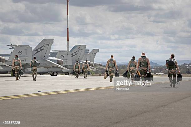 In this handout image provided by Commonwealth of Australia F/A18F Super Hornet aircrew walk to their aircraft in preparation for departure to the...