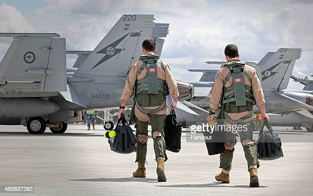 In this handout image provided by Commonwealth of Australia F/A18F Super Hornet aircrew head to their aircraft in preparation for departure to the...