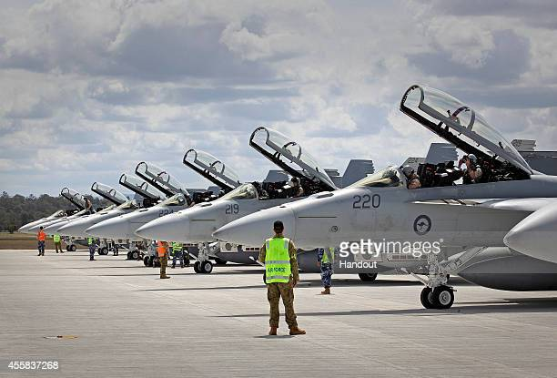 In this handout image provided by Commonwealth of Australia, ground crew assist as RAAF F/A-18F Super Hornets prepare for departure to the Middle...