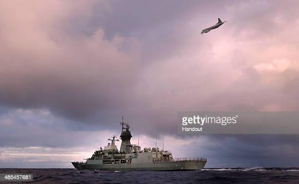 In this handout image provided by Commonwealth of Australia, HMAS Perth transits through the Southern Indian Ocean as an Orion P-3K of the Royal New...
