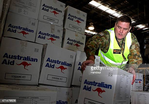 In this handout image provided by Commonwealth of Australia Department of Defence Warrant Officer Jamie Auld loads Australian Aid for delivery to...