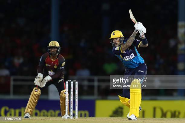 In this handout image provided by CPL T20, Alex Hales of Barbados Tridents hits four as Denesh Ramdin of Trinbago Knight Riders looks on during the...