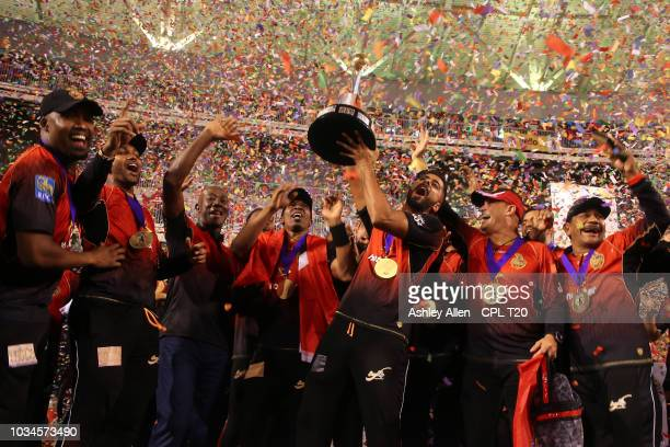 In this handout image provided by CPL T20 Ali Khan of Trinbago Knight Riders celebrates teammates as he lifts the winners trophy during the Hero...