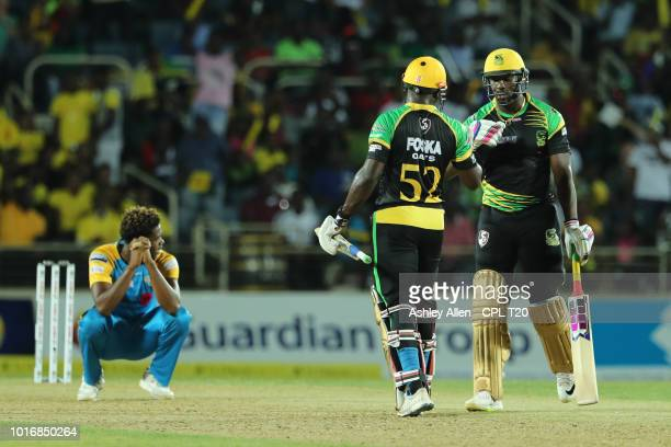 In this handout image provided by CPL T20 Andre Russell and Rovman Powell of Jamaica Tallawahs congratulate eachother as Obed McCoy of St Lucia Stars...