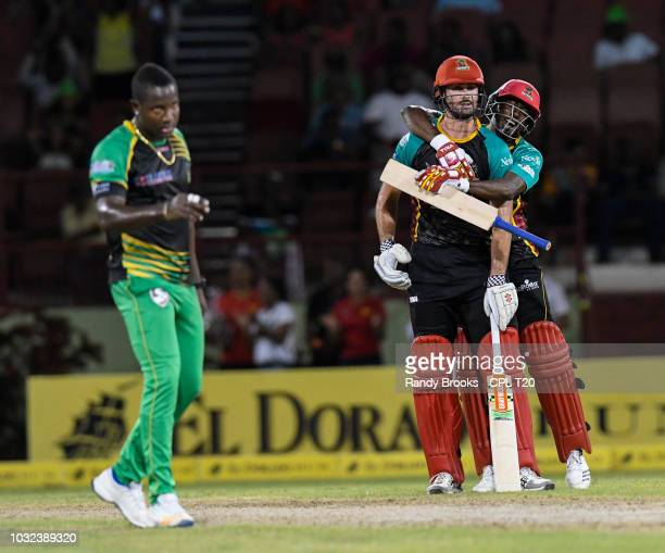 In this handout image provided by CPL T20 Ben Cutting and Hayden Walsh Jr of St Kitts Nevis Patriots celebrate as Rovman Powell of Jamaica Tallawahs...