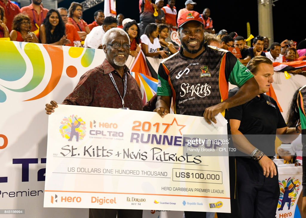 In this handout image provided by CPL T20, Chris Gayle (R) of St Kitts & Nevis Patriots receives the runners-up cheque from Most Hon. PJ Patterson (L) of CPL after the Finals of the 2017 Hero Caribbean Premier League between Trinbago Knight Riders and St Kitts & Nevis Patriots at Brian Lara Cricket Academy on September 09, 2017 in Tarouba, Trinidad.