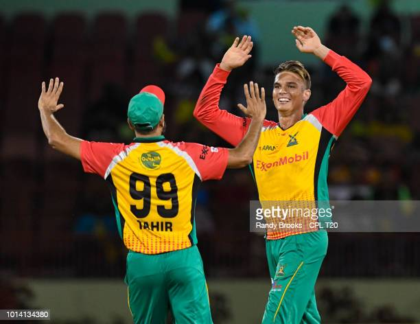 In this handout image provided by CPL T20 Chris Green and Imran Tahir of Guyana Amazon Warriors celebrates the dismissal of Evin Lewis of St Kitts...