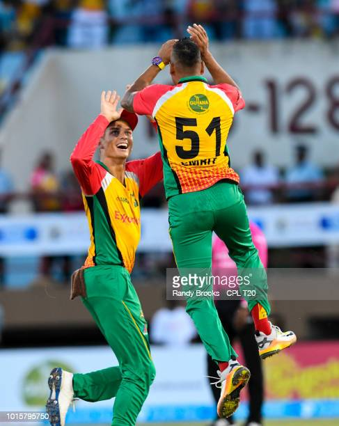 In this handout image provided by CPL T20 Chris Green and Rayad Emrit of Guyana Amazon Warriors celebrate the dismissal of Martin Guptill of Barbados...
