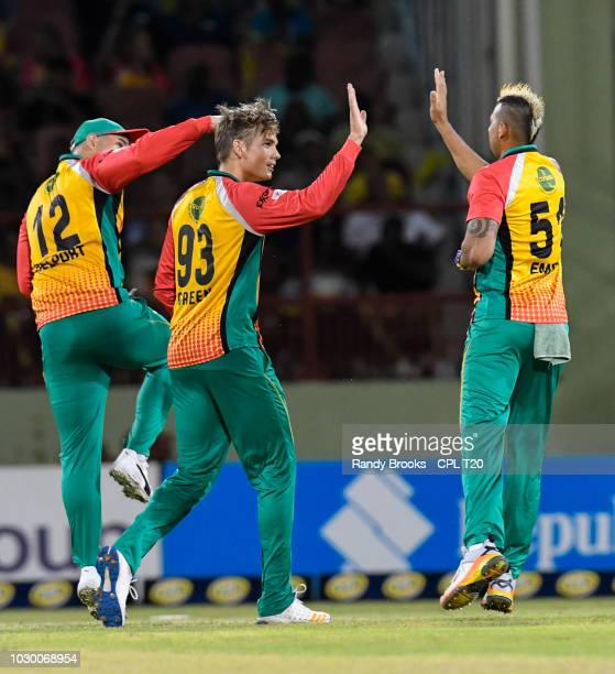 In this handout image provided by CPL T20 Chris Green Cameron Delport Rayad Emrit of Guyana Amazon Warriors celebrate the dismissal of Colin Ingram...