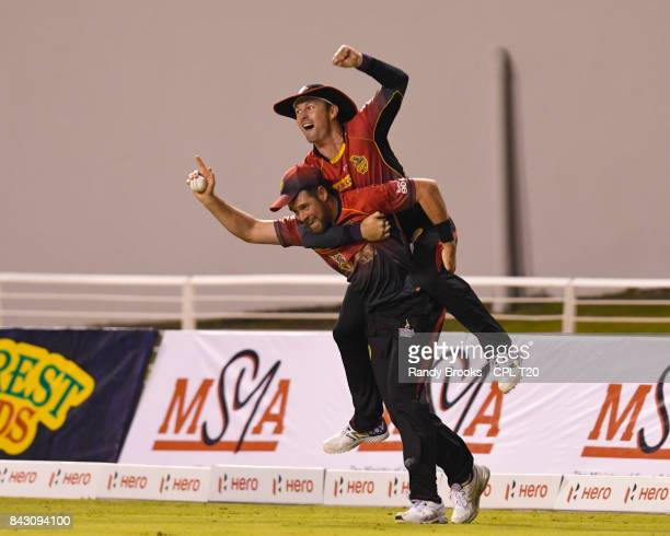 In this handout image provided by CPL T20 Daniel Christian and Colin Munro of Trinbago Knight Riders celebrate the dismissal of Evin Lewis of St...