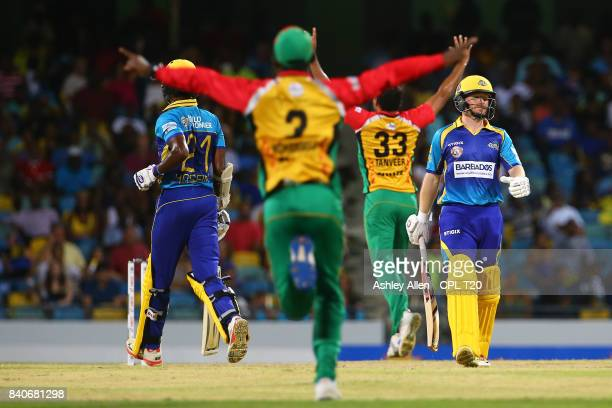 In this handout image provided by CPL T20 Eoin Morgan of Barbados Tridents is given out LBW as Jason Mohammed and Sohail Tanvir of the Guyana Amazon...