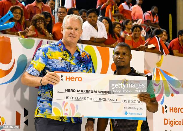 In this handout image provided by CPL T20 Evin Lewis of St Kitts Nevis Patriots receives a cheque from Tom Moody of CPL after the Finals of the 2017...