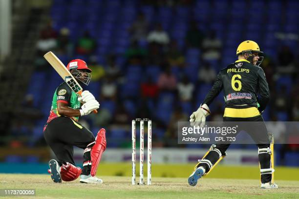 In this handout image provided by CPL T20, Evin Lewis of St Kitts and Nevis Patriots sweeps four four during the Hero Caribbean Premier League match...