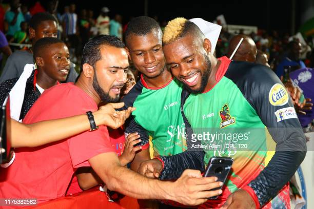 In this handout image provided by CPL T20, Fabian Allen and Evin Lewis of St Kitts and Nevis Patriots pose for a photo with a fan after the Hero...
