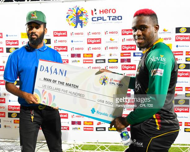 In this handout image provided by CPL T20 Fabian Allen of St Kitts Nevis Patriots receives the man of the match prize from Michael Henry Perez during...