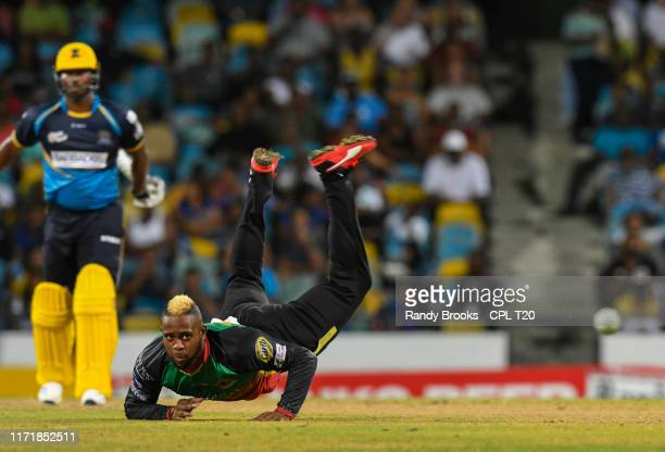 In this handout image provided by CPL T20, Fabian Allen of St Kitts Nevis and Patriots attempts to stop Johnson Charles of Barbados Tridents from...