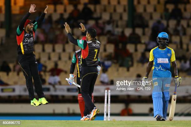 In this handout image provided by CPL T20 From left Tabraiz Shamsi and Mohammed Nabi of the St Kitts and Nevis Patriots celebrate the wicket of Andre...