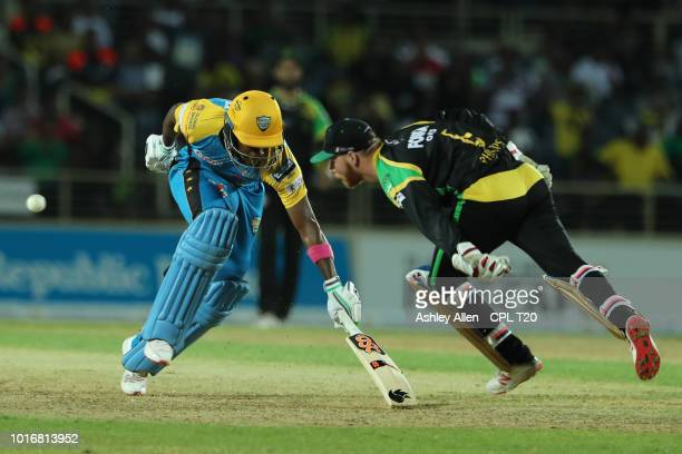 In this handout image provided by CPL T20 Glenn Phillips of Jamaica Tallawahs attempts to collect a poor return throw as Kavem Hodge of St Lucia...