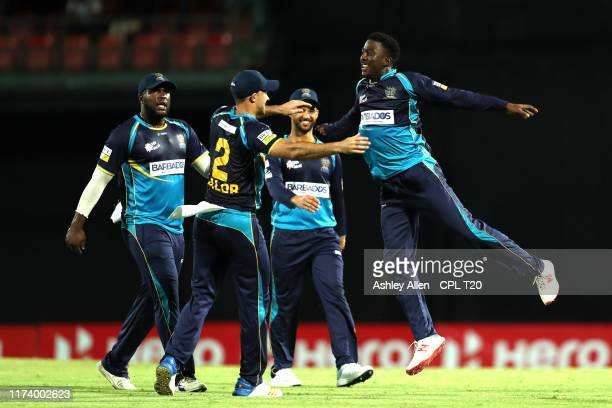 In this handout image provided by CPL T20, Hayden Walsh of Barbados Tridents celebrates with teammates after getting the wicket of Fabian Allen of St...