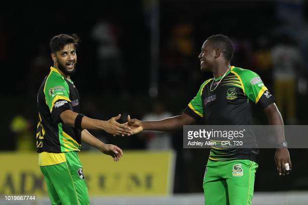 In this handout image provided by CPL T20 Imad Wasim is congratulated by teammate Rovman Powell of Jamaica Tallawahs during the Hero Caribbean...