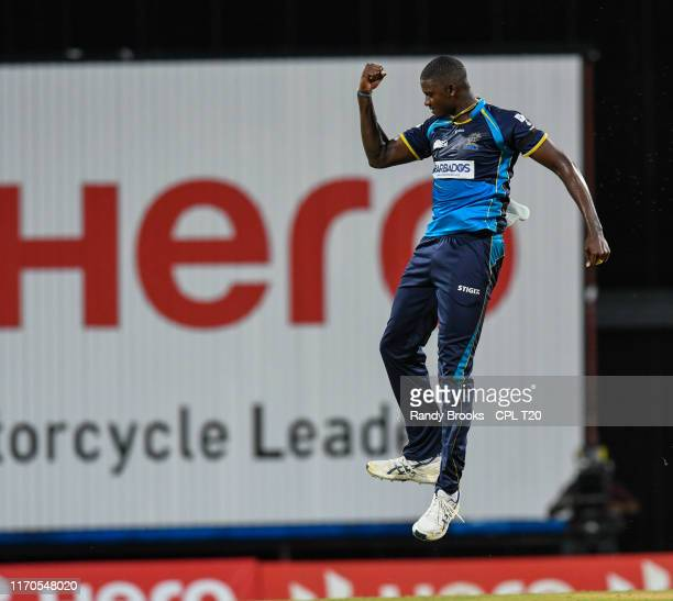 In this handout image provided by CPL T20, Jason Holder of Barbados Tridents celebrates the dismissal of Chris Gayle of Jamaica Tallawahs during...