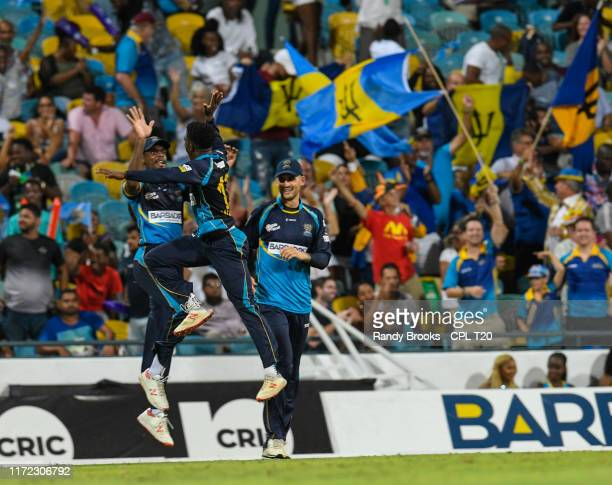 In this handout image provided by CPL T20 Justin Greaves Hayden Walsh Jr and Alex Hales of Barbados Tridents celebrate the dismissal of Darren Sammy...