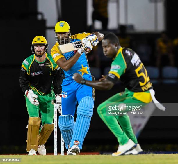 In this handout image provided by CPL T20 Kieron Pollard of St Lucia Stars hits pass Rovman Powell as Glenn Phillips of Jamaica Tallawahs watch...