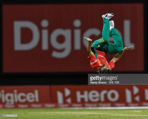 In this handout image provided by CPL T20 Qais Ahmad of Guyana Amazon Warriors celebrates the dismissal of Dwayne Smith of Jamaica Tallawahs during...