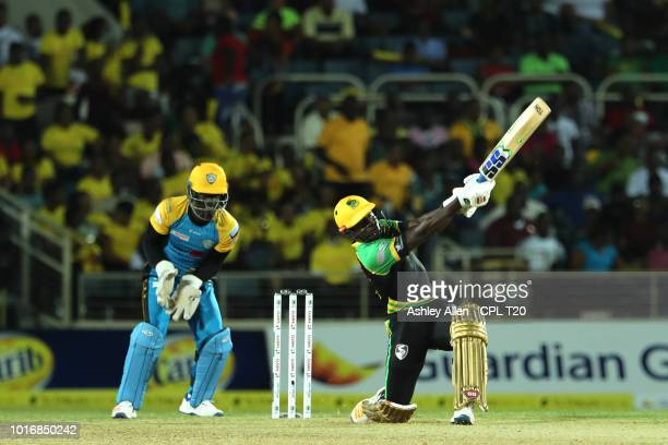 In this handout image provided by CPL T20 Rovman Powell of Jamaica Tallawahs hits six as Andre Fletcher of St Lucia Stars looks on during the Hero...