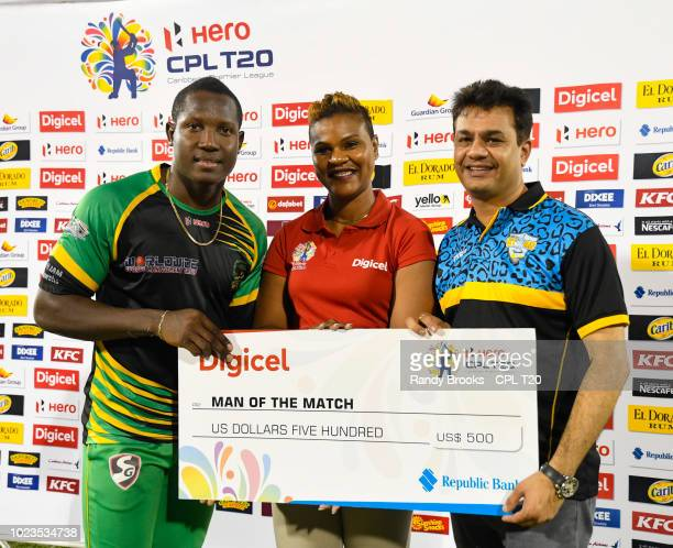 In this handout image provided by CPL T20 Rovman Powell of Jamaica Tallawahs receives the man of the match prize from Siobhan JamesAlexander of...
