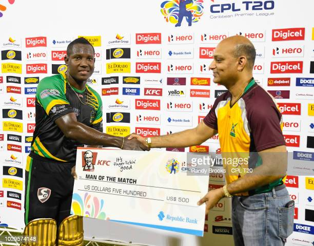 In this handout image provided by CPL T20 Rovman Powell of Jamaica Tallawahs receives the man of the match prize from Anil Beharry of KFC during...