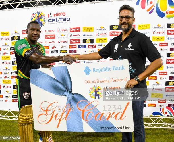 In this handout image provided by CPL T20 Rovman Powell of Jamaica Tallawahs receives the Republic Bank gift card from Richard Sammy during match 29...