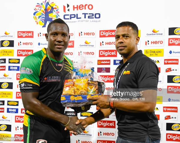 In this handout image provided by CPL T20 Rovman Powell of Jamaica Tallawahs receives the Sunshine Snacks prize from Jerazeno Bell at the end of...