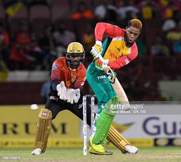 In this handout image provided by CPL T20 Shimron Hetmyer of Guyana Amazon Warriors hits 4 and Denesh Ramdin of Trinbago Knight Riders watch during...