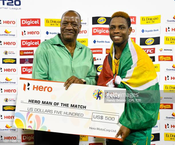 In this handout image provided by CPL T20 Shimron Hetmyer of Guyana Amazon Warriors receives the man of the match prize from Joseph Harmon Minister...