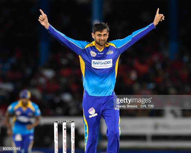 In this handout image provided by CPL T20 Shoaib Malik of Barbados Tridents celebrates the dismissal of Colin Munro of Trinbago Knight Riders during...