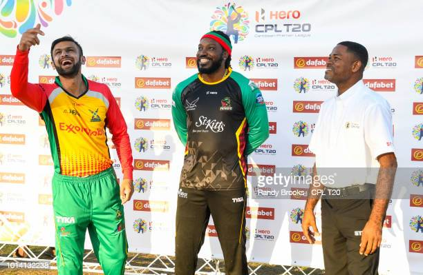 In this handout image provided by CPL T20 Shoaib Malik of Guyana Amazon Warriors toss the coin as Chris Gayle St Kitts Nevis Patriots and match...