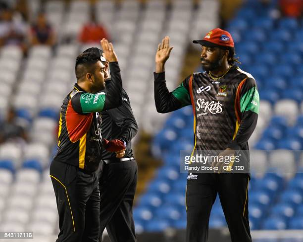 In this handout image provided by CPL T20 Tabraiz Shamsi and Chris Gayle of St Kitts Nevis Patriots celebrate the dismissal of Shadab Khan of...