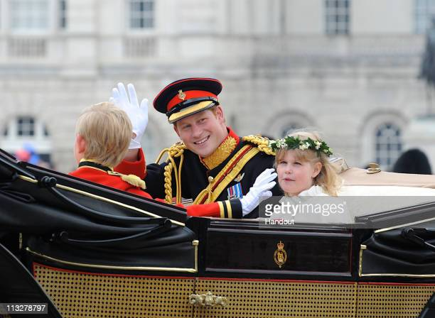 In this handout image provided by Crown Copyright Prince Harry waves to the crowd as they make the journey by carriage procession to Buckingham...