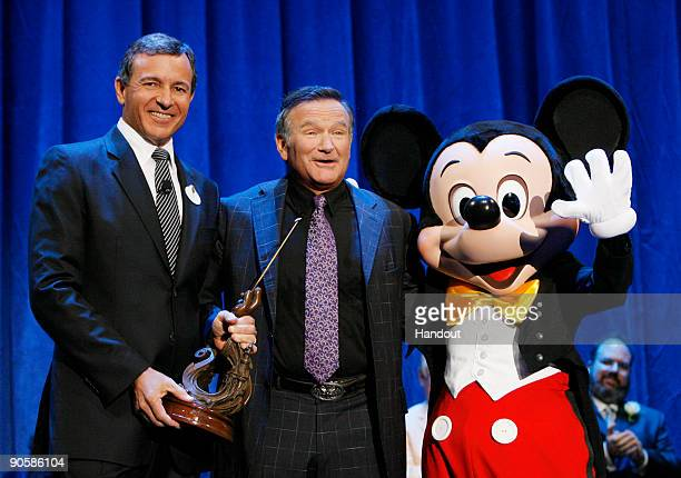 In this handout image provided by Disney actor Robin Williams is recognized by Bob Iger CEO of Walt Disney Coand Mickey Mouse for Williams' work in...