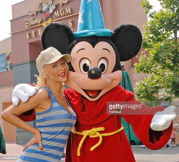 In this handout image provided by Disney grammy Awardwinning artist Christina Aguilera poses with Mickey Mouse at the DisneyMGM Studios on May 3 2007...