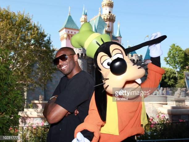 In this handout image provided by Disney Los Angeles Lakers star Kobe Bryant celebrates the Lakers' NBA championship with Goofy at Disneyland on June...