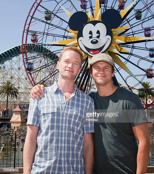 In this handout image provided by Disney Neil Patrick Harris and David Burtka pose at Paradise Pier in Disney California Adventure on August 14 2010...