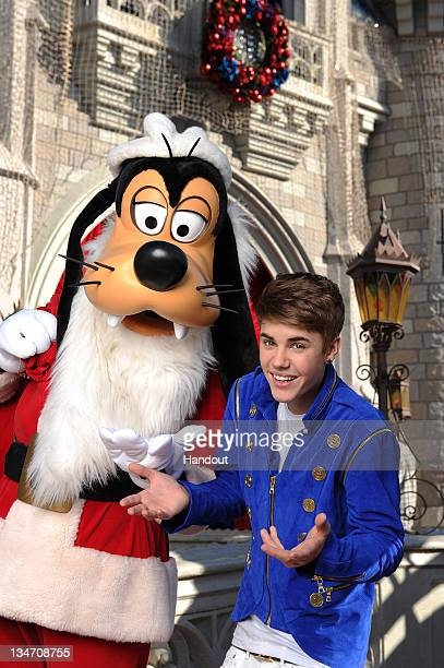 In this handout image provided by Disney Parks Justin Bieber poses with Santa Goofy during a break while taping a performance segment for the 'Disney...